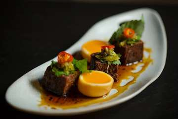 """We know it's a favourite. Crispy pork hock """"par low style"""" with master stock caramel duck egg pickled chili and mustard green."""